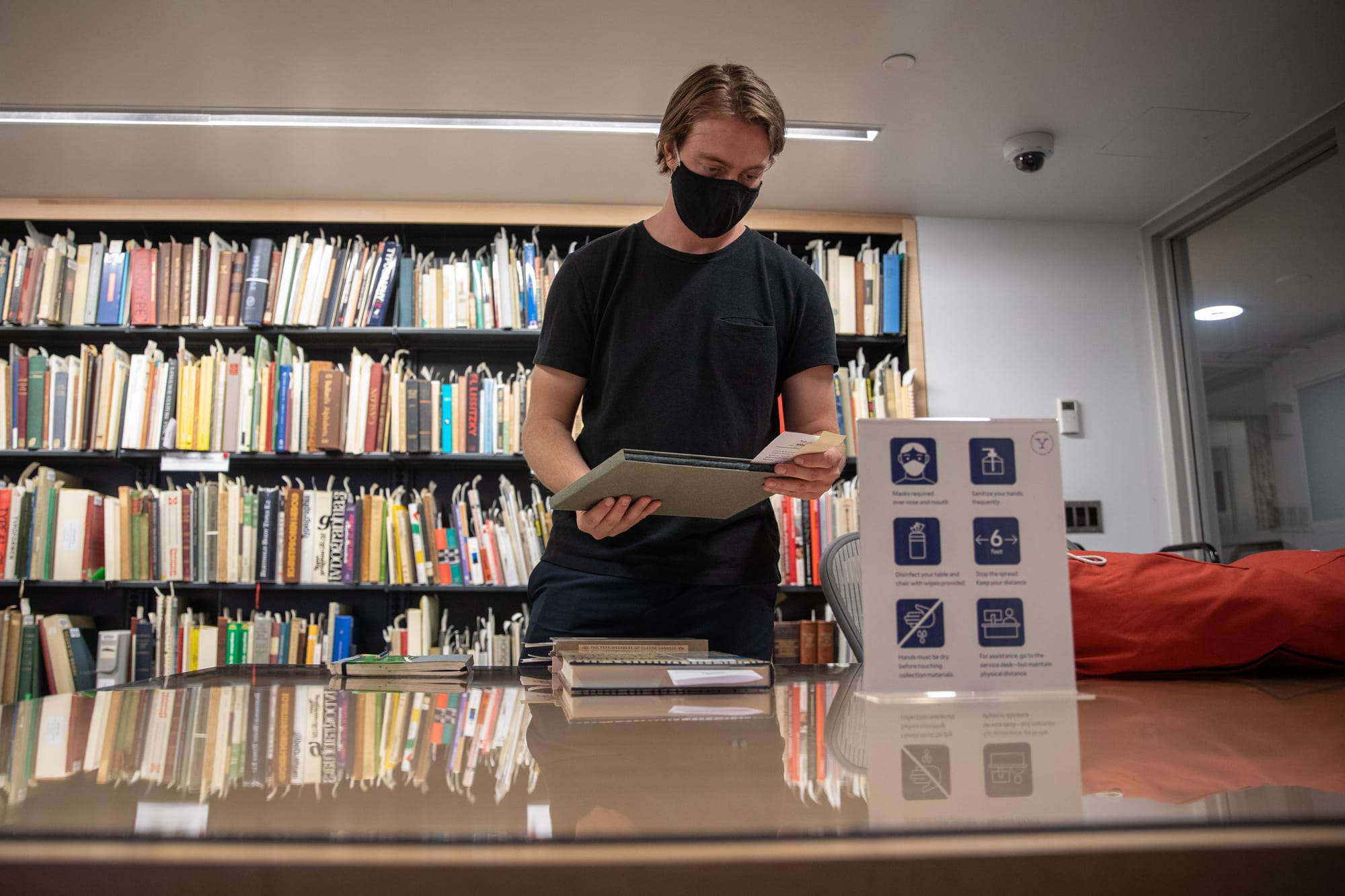 A masked student stands in front of book shelves and behind a table stacked with library books. Photo by Andrew Hurley