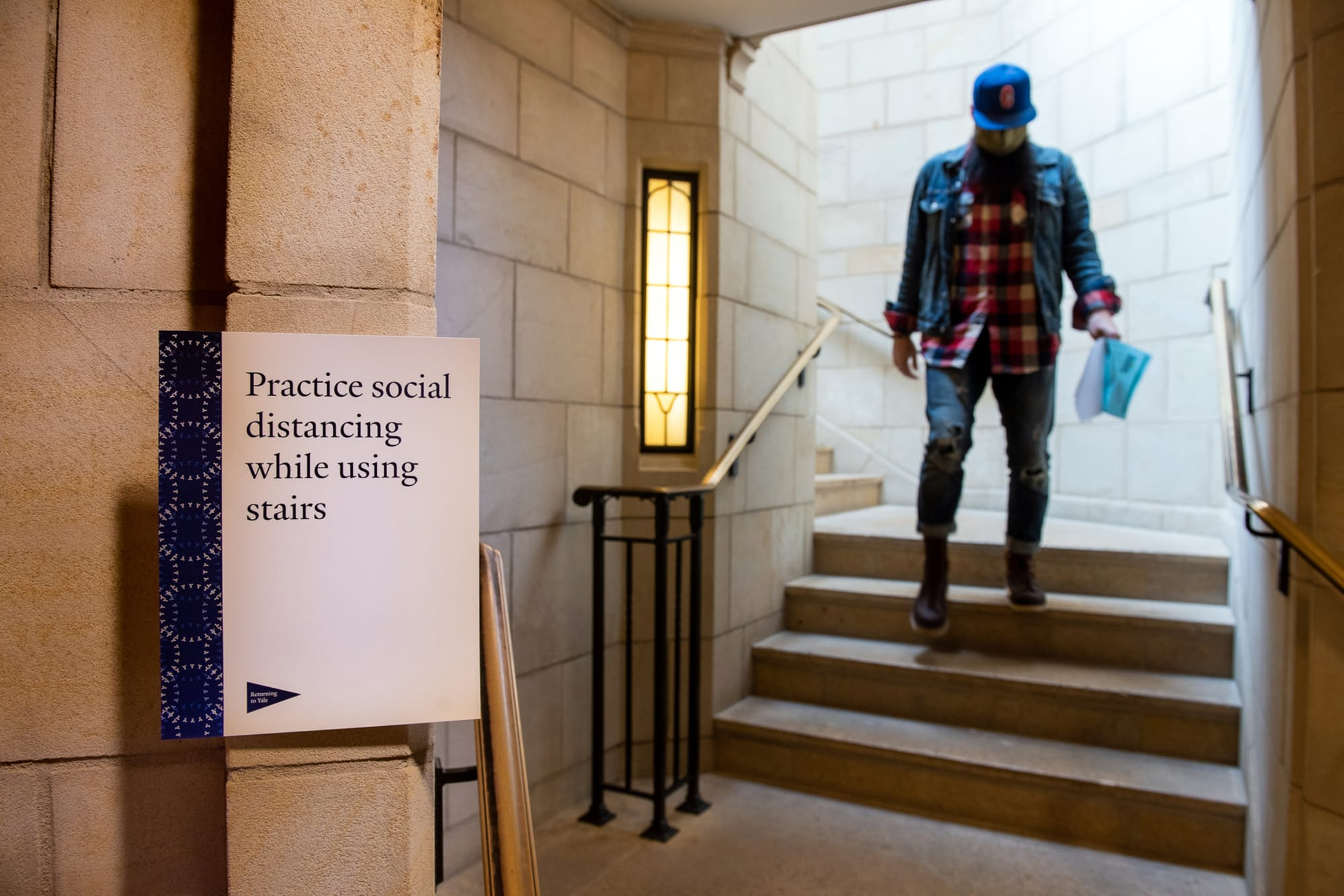 Man descending stair from Sterling nave with physical distancing signage in foreground  Photo by Mara Lavitt