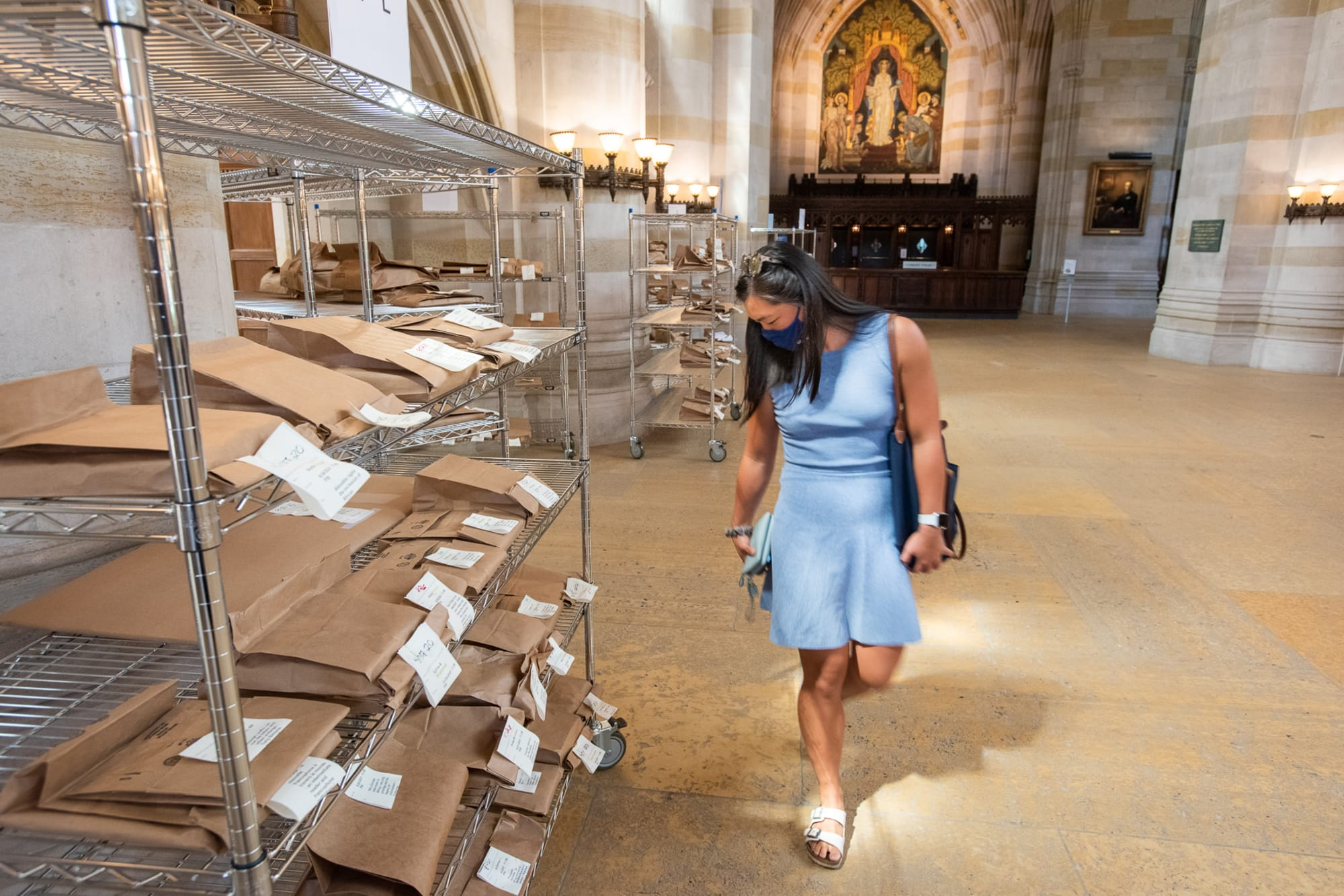 Woman in a blue dress looks at metal racks of brown paper bags in Sterling nave.  Photo by Mara Lavitt
