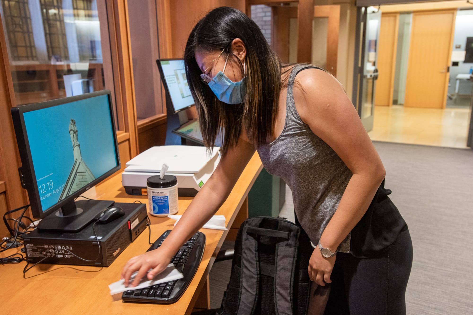 Woman cleans computer keyboard with wipes in Bass Library. Photo by Mara Lavitt