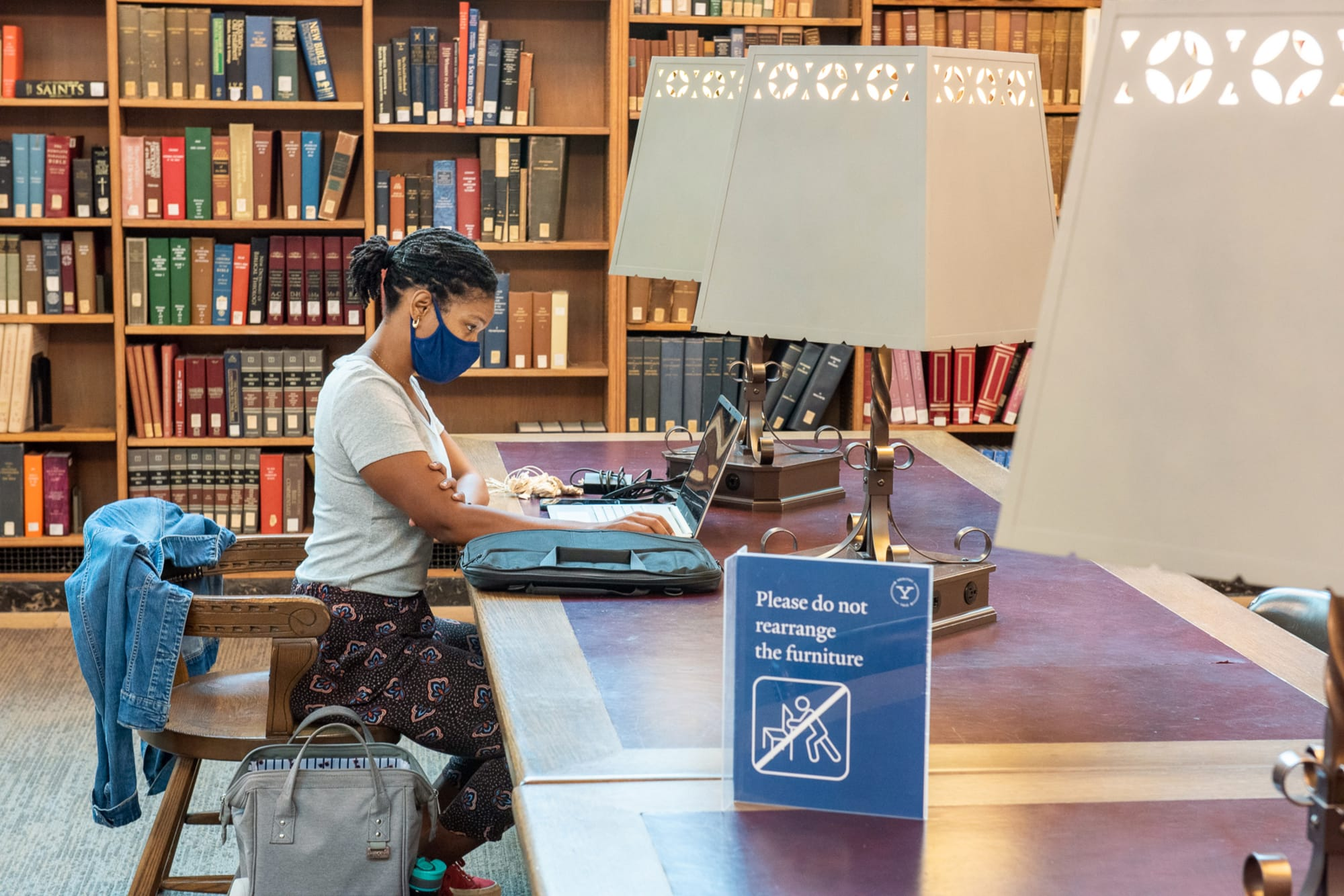 Student sitting with laptop at a wooden table in the Starr Reading Room, with public health signage in foreground. Photo by Mara Lavitt