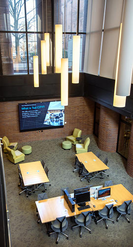 view from above of two-story study space with hanging lights, desks, computers