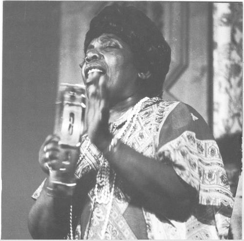Black and white photo of Bessie Jones holding a microphone and singing