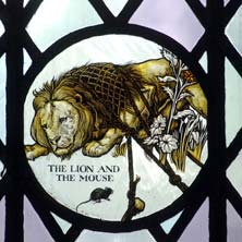 Stained glass picturing Aesop's The Lion and the Mouse