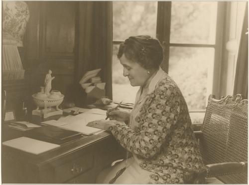 Black and white photo of Edith Wharton at her writing desk