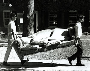 Two male students moving a couch across campus.