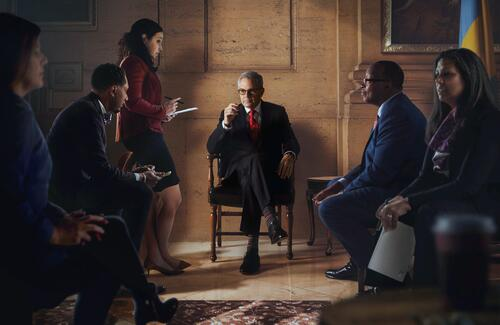 photo of Larry Krasner in an office surrounded by advisors