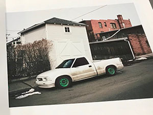photo book page showing parked car in front of buildings