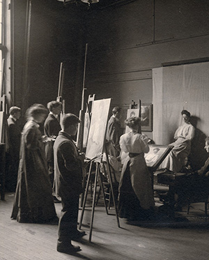 A black and white photograph of Yale art students standing at easels paitning a live model