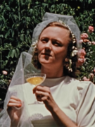 Cynthia Childs in a wedding dress holding a glass of champagne in the film Seductio Ad Absurdum