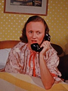 color photo of filmmaker Cynthia Childs on a bed, talking on the phone
