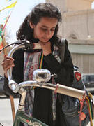Young actress looks at a bicycle in the film Wadjda.