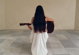 still of Meredith Monk holding a guitar from the film 16 Millimeter Earrings
