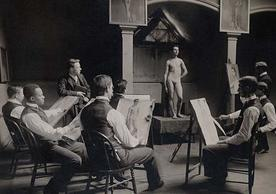 Black and white photo of male artists sketching female model