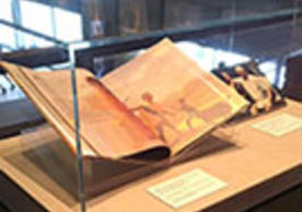 Exhibit case with three items related to Mandela from Yale library collections, a book, a photo and a poster.