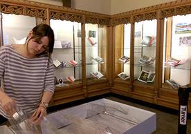 "Elizabeth Morris installing 2016 ""Moving Earth"" exhibit in Memorabilia Room"