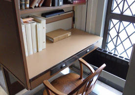 A carrel in the tower of Sterling Memorial Library, with a chair and small cubicle seating.