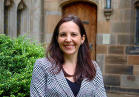 Woman with dark hair and plaid jacket against backdrop of Gothic library builiding