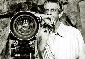 black and white photo of Satyajit Ray standing next to a movie camera