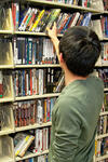Patron with back to camera examines shelves of videos