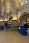 Library staff with books carts and racks of bagged library material in Sterling Library nave